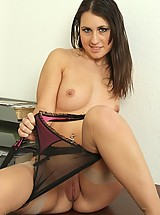 Jess West at her desk in stockings and suspenders